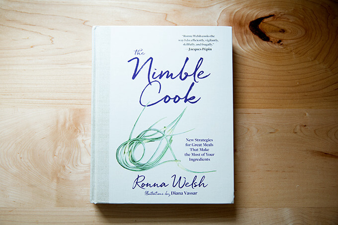 A cookbook, The Nimble Cook, on a counter.