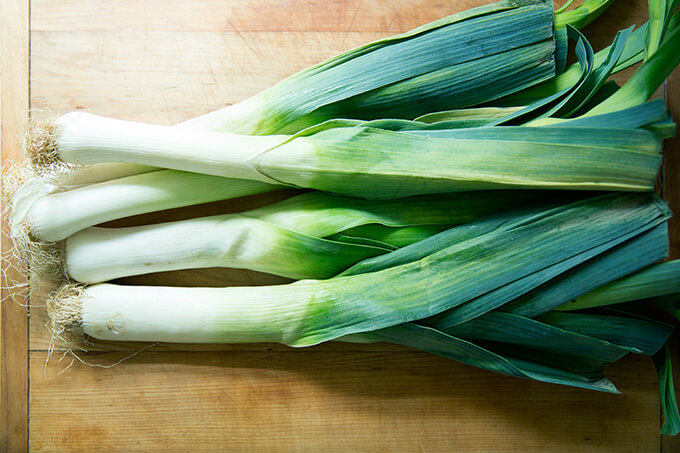 Whole leeks on a cutting board.