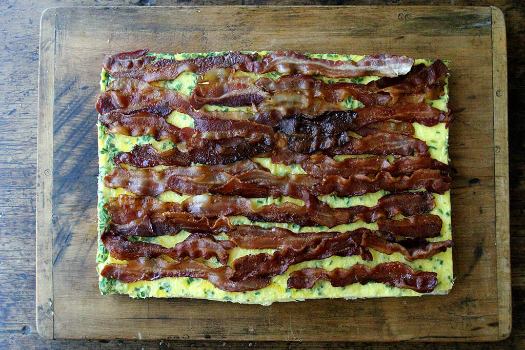 Adding the bacon to the sheet pan sandwich.