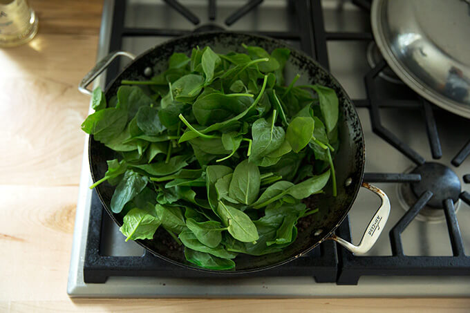 A skillet with lentils, onions, and a heap of spinach.