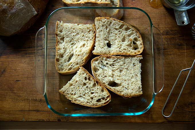 Slices of sourdough soaking in olive oil and vinegar in a square 8-inch pan.