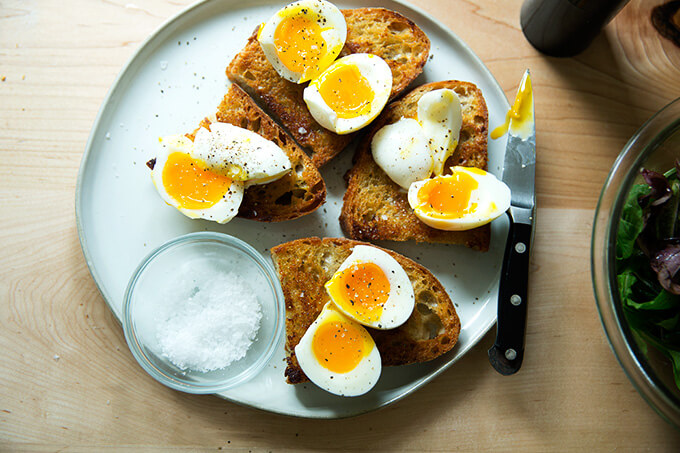 A plate of cut eggs on vinaigrette toast, seasoned.