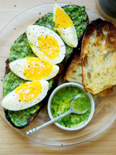 A plate of toasted sourdough smeared with green sauce, topped with 7-minute eggs.