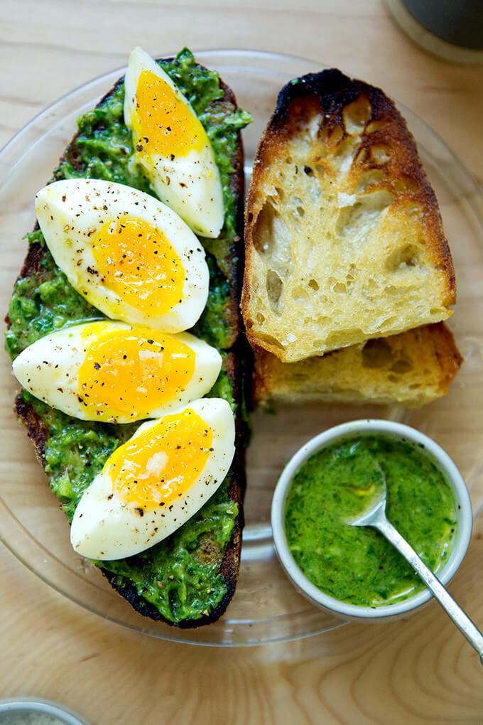 A plate of toasted sourdough bread with green sauce, and 7-minute eggs.