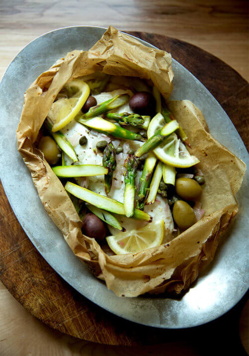 A sizzle pan with an opened fish en papillote.