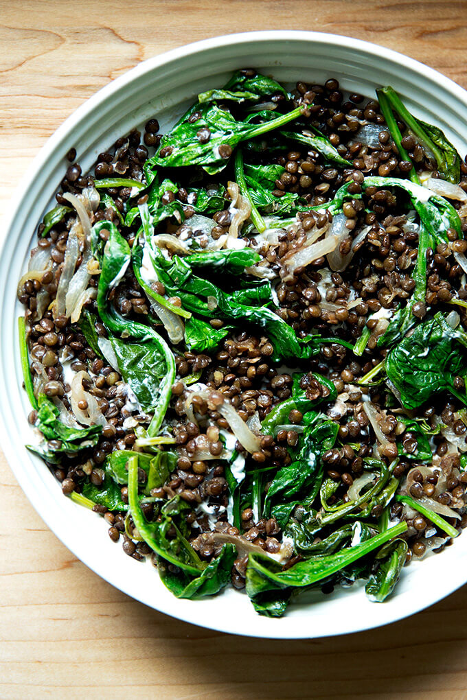 A bowl of black lentils with spinach and labneh.