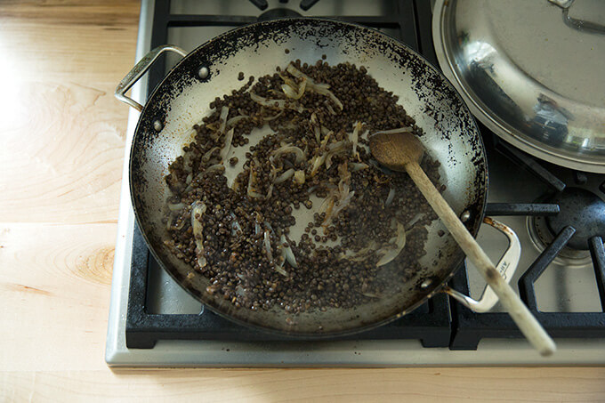A skillet with lentils and onions.