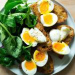 A plate of vinaigrette toasts topped with soft-boiled eggs aside dressed arugula.