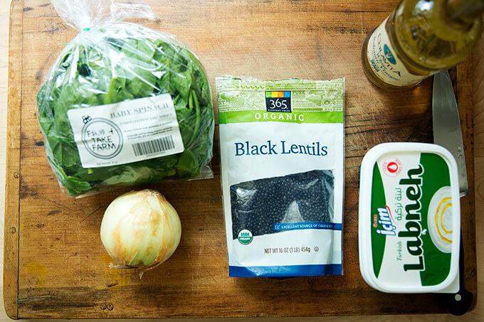 A cutting board with the ingredients to make black lentils with spinach.