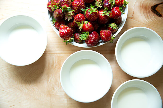 A bowl of strawberries + 4 bowls of cream.