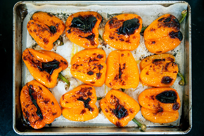 A sheet pan with blistered orange bell peppers.