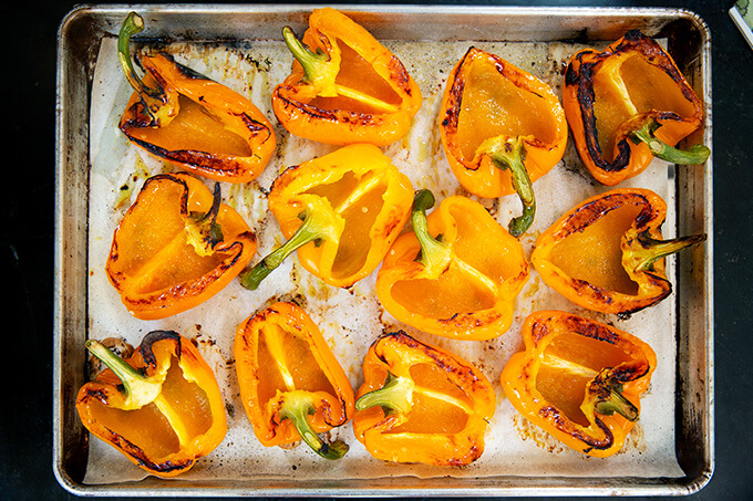A sheet pan with blistered orange bell peppers cut side up.