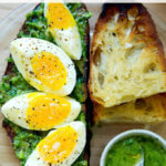 A slice of toast topped with herby green sauce and 7-minute eggs.