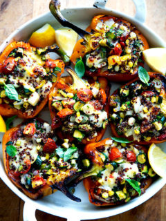 Roasted bell peppers stuffed with quinoa and sautéed corn, zucchini, and tomatoes.