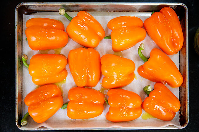 A sheet pan of halved orange bell peppers cut side down.