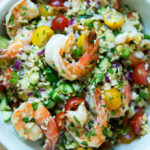 A bowl of tabbouleh with cilantro, lime, and grilled shrimp.