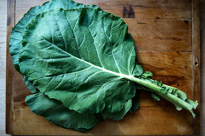 A bunch of collard greens on a board.