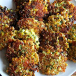 Corn fritters with cheddar and scallions on a platter.