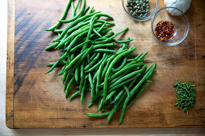 A cutting board with stemmed green beans, capers, garlic, and chili flakes.