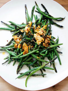 A plate of spicy, blistered green beans with garlic.