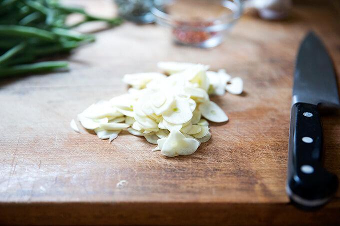 Sliced garlic on a board.