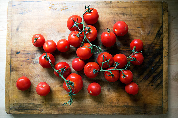 Tomatoes on the vine on a cutting board.