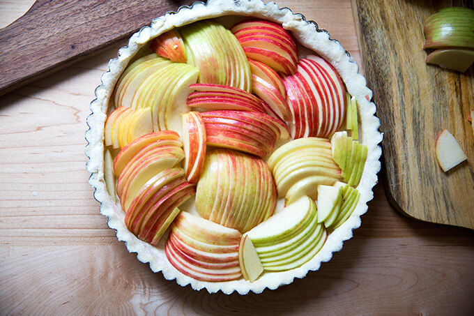 An unbaked French apple tart shell filled with sliced apples.