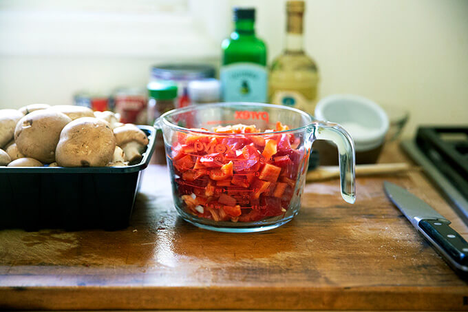 A liquid measure filled with chopped red bell peppers.