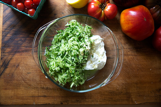 Grated cucumber and yogurt in a large bowl.