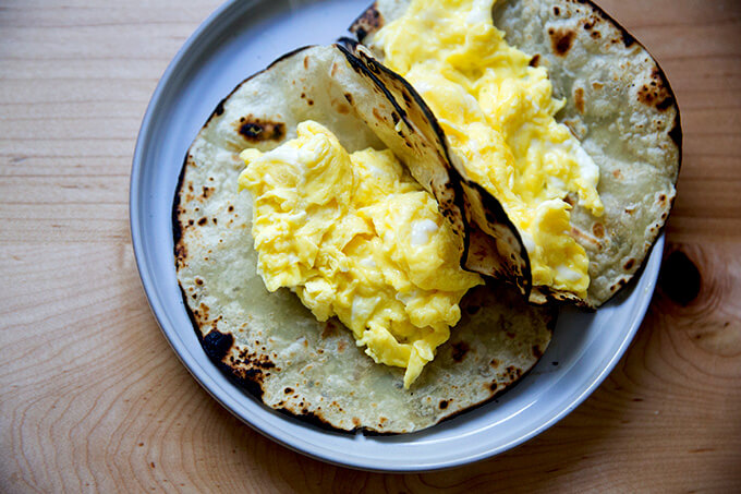 Two flour tortillas filled with scrambled eggs.