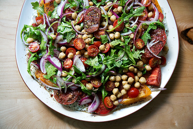 A platter of Israeli spiced tomato salad with cucumber yogurt sauce and chickpeas.