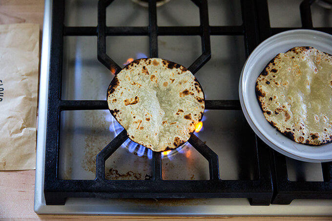 Charring the tortillas over a gas flame.