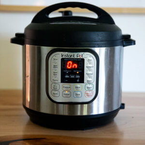 An Instant Pot on a counter turned on.