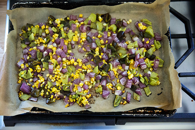 Roasted vegetables on a sheet pan lined with parchment paper.
