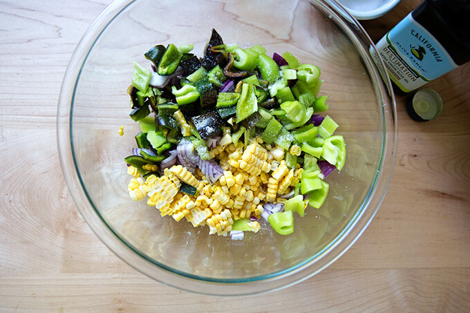 A bowl of raw corn, poblanos, red onion, olive oil, and salt.