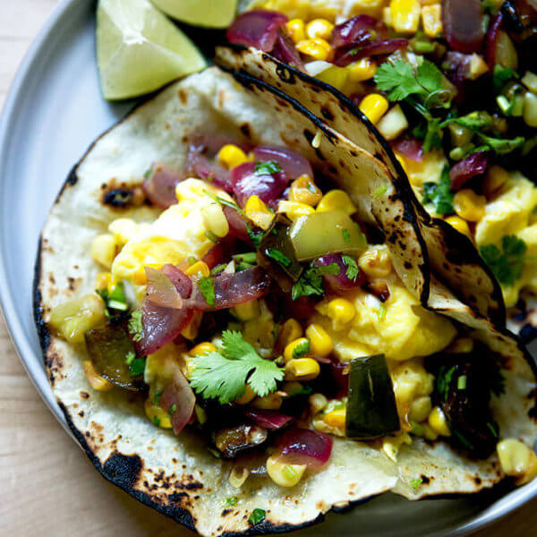 A plate of an egg taco topped with roasted vegetable salsa.