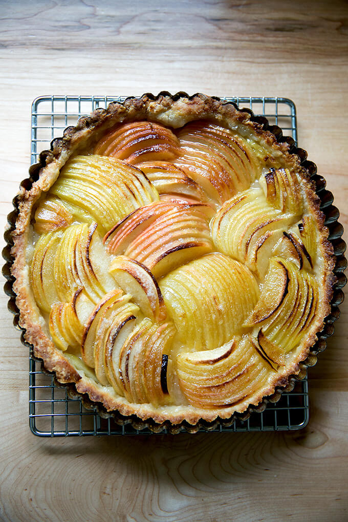 A French apple tart just baked on a cooling rack.