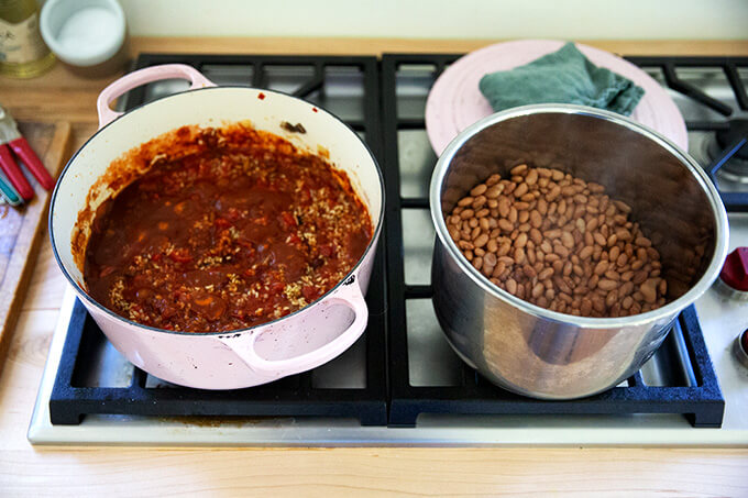 Two pots on the stove: one with vegetarian chili; the other with cooked Instant pot pinto beans.