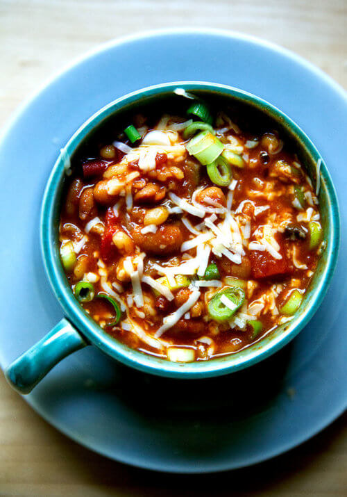 A bowl of spicy, smoky stovetop vegetarian chili with cheese and scallions stirred in.