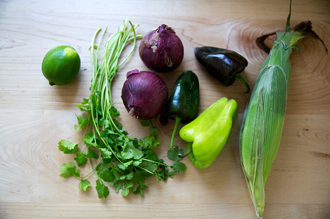 vegetables on a countertop: lime, cilantro, onions, poblano peppers, and corn