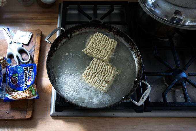 A sauté pan on the stovetop filled with boiling water and ramen noodles.