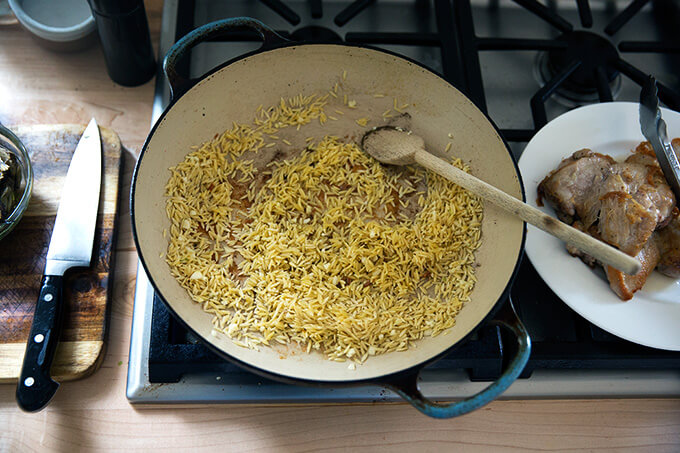 A skillet with orzo toasting in olive oil.