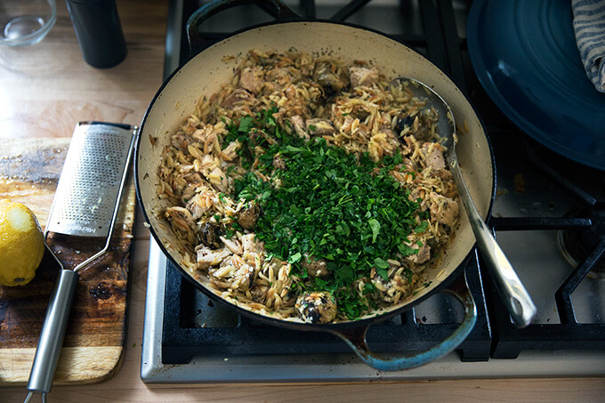 A skillet on the stovetop with chicken, orzo, artichokes, cheese, and, parsley