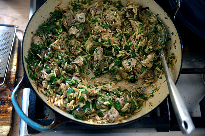 A skillet on the stovetop with chicken, orzo, artichokes, cheese, and, parsley all stirred together.