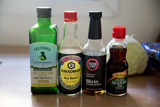 Four bottles standing in a row on a countertop: olive oil, soy sauce, mirin, and sesame oil.