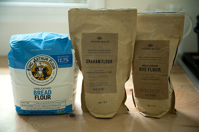 Three flours on a counter top: King Arthur Flour bread flour, Anson Mills Graham Flour, Anson Mills Rye flour.