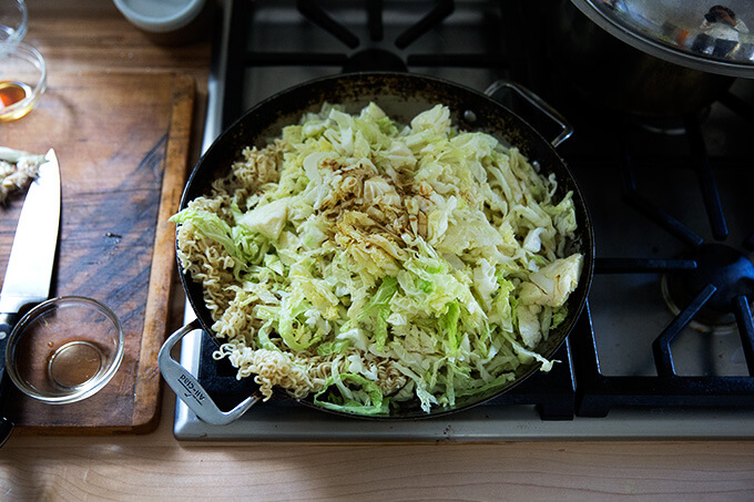 A large sauté pan filled with mushrooms, ginger, cabbage, and noodles.