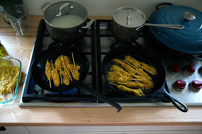 Two cast iron skillets on a stovetop cooking easy Thai chicken satay.