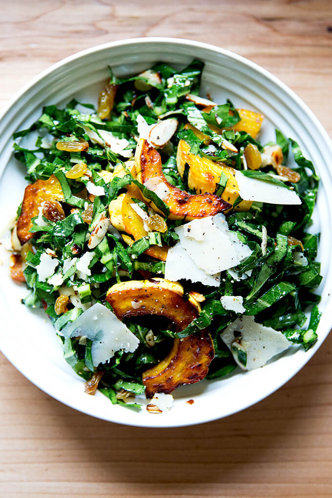 A bowl of raw collard greens salad with roasted delicata squash, golden raisins, shaved parmesan, and toasted almonds.