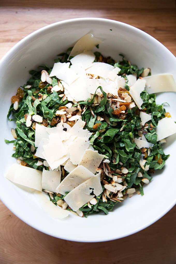 A bowl of shaved collard greens, almonds, golden raisins, and shaved parmesan.